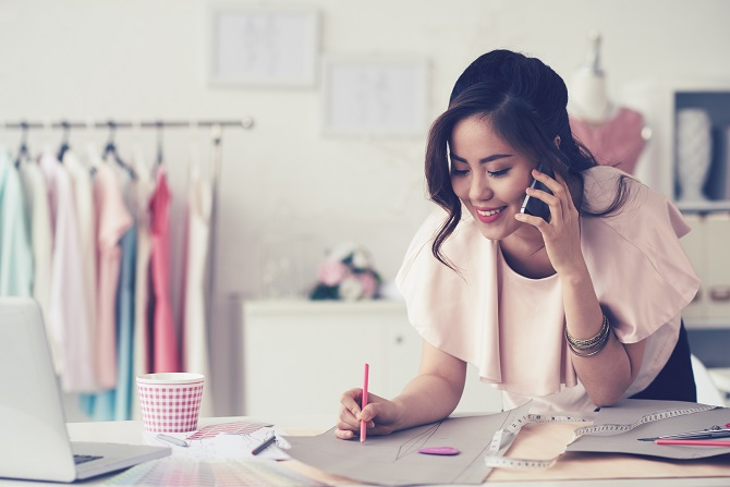 Young fashion designer making pattern and talking on the phone